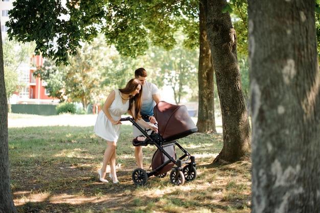 Heureux jeunes parents marchant dans le parc avec landau