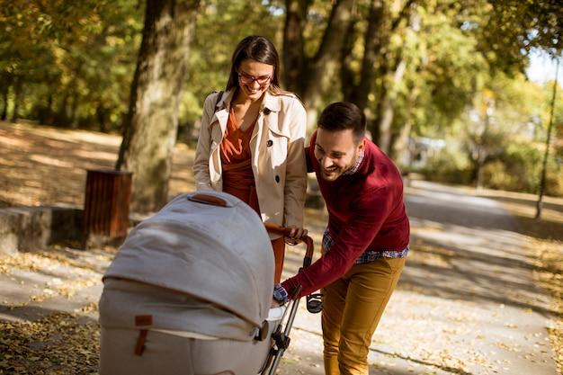 Heureux jeunes parents se promener dans le parc et conduire un bébé en landau