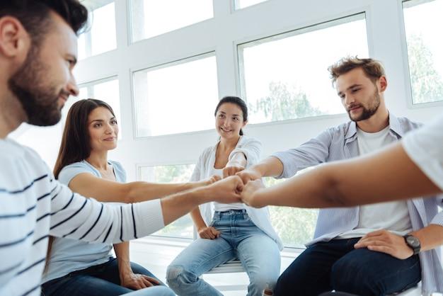 Heureux jeunes positifs assis dans le cercle et faisant une activité de teambuilding tout en apprenant à travailler ensemble