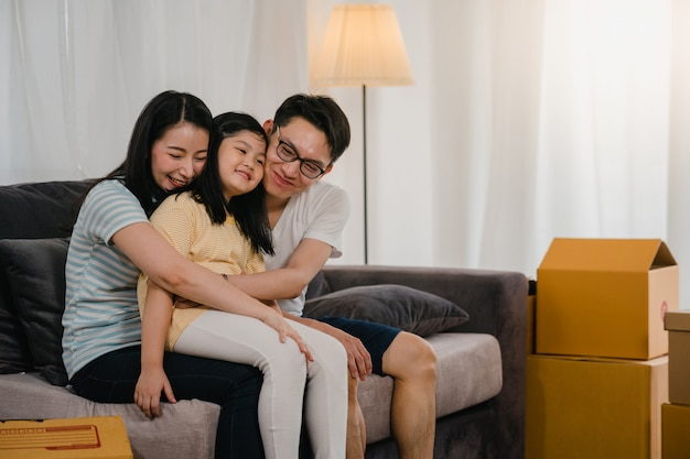 Heureux jeunes propriétaires asiatiques ont acheté une nouvelle maison. une mère japonaise, un père et sa fille s'embrassent dans le nouveau foyer après avoir déménagé, assis sur un canapé et des boîtes ensemble.
