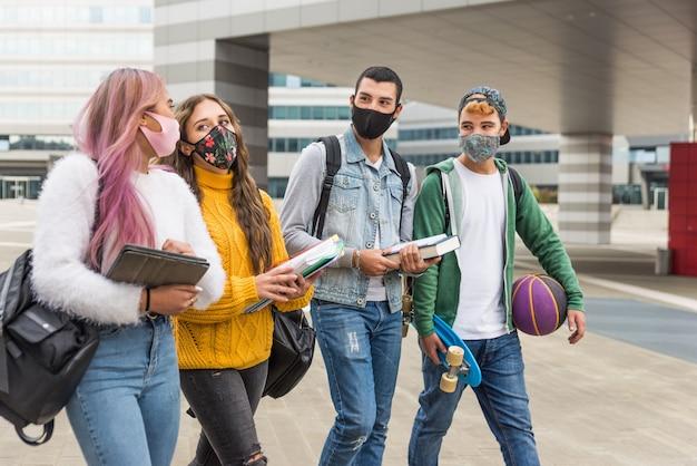 Heureux les jeunes se réunissant à l'extérieur et portant des masques pendant la pandémie de covid-19