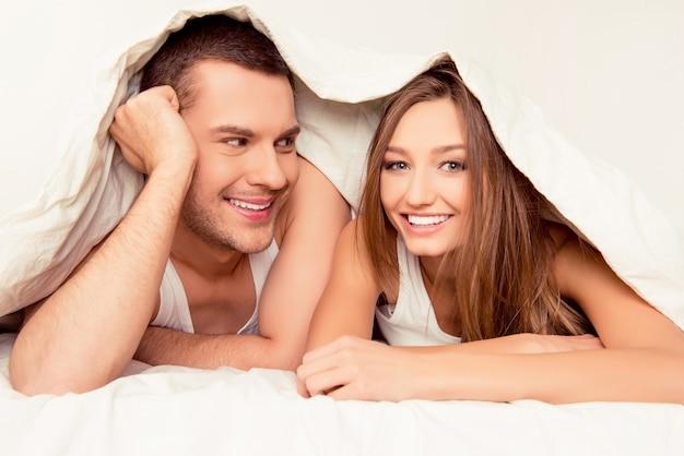 Heureux joli homme et femme couchée sous une couverture le matin