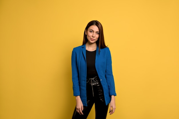 Heureux jolie femme aux cheveux longs, yeux foncés et peau saine vêtue d'une veste bleue, souriant tout en posant contre le mur de béton jaune. les gens et le style de vie