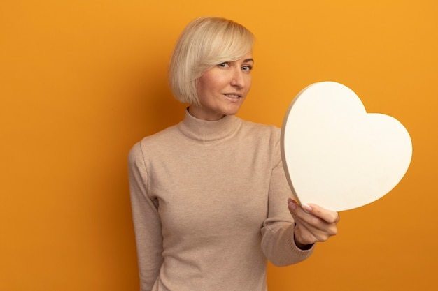 Heureux jolie femme slave blonde tient en forme de coeur à l'avant isolé sur mur orange