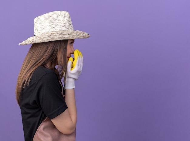 Heureux jolie jardinière caucasienne portant un chapeau et des gants de jardinage se tient sur le côté, tenant la main près de la bouche