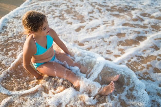 Heureux jolie petite fille bénéficie de l'eau de mer chaude située au bord de la plage de sable par une chaude journée d'été ensoleillée