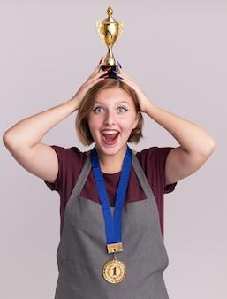 Heureux et joyeux jeune coiffeur belle femme en tablier avec médaille d'or autour du cou tenant le trophée d'or sur sa tête regardant à l'avant avec un grand sourire sur le visage debout sur un mur blanc