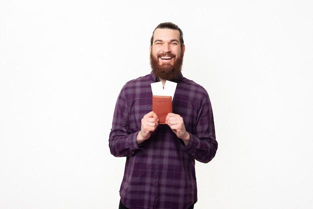 Heureux et joyeux jeune homme barbu tenant un passeport et des billets de voyage