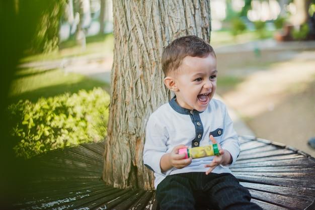 Heureux junior garçon dans le jardin par une journée ensoleillée