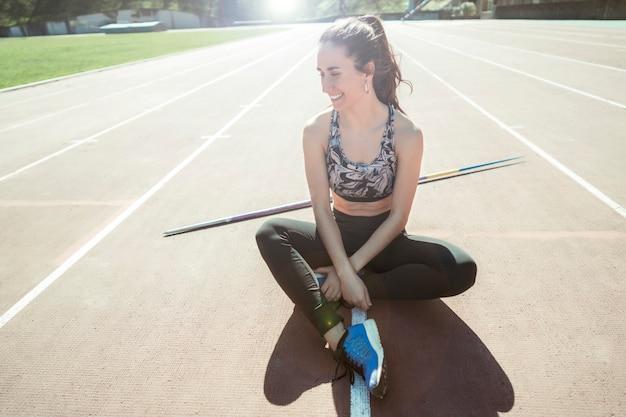 Heureux lanceur de javelot femme assise sur une piste
