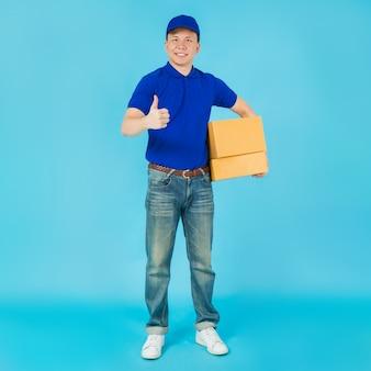 Heureux livreur asiatique portant une chemise bleue et un chapeau montrant les pouces vers le haut et transportant une boîte à colis en papier.