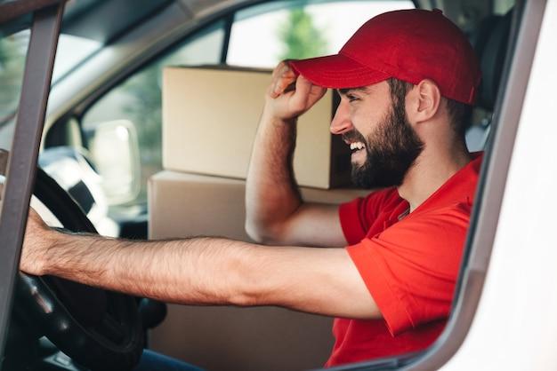 Heureux livreur barbu en uniforme rouge souriant et conduisant une camionnette avec des boîtes à colis