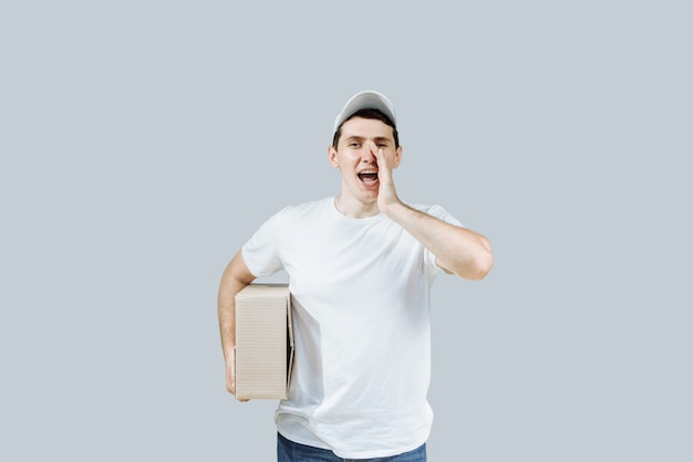 Heureux livreur avec une boîte en uniforme.