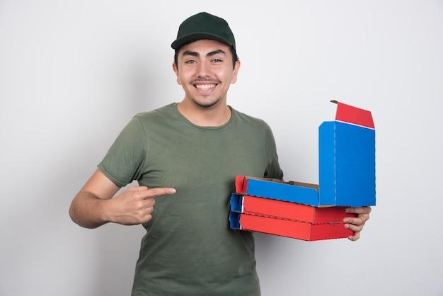 Heureux livreur pointant sur les boîtes de pizza sur fond blanc.