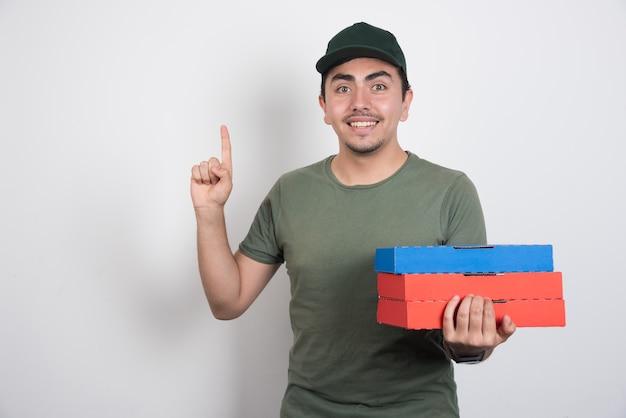 Heureux livreur pointant vers le haut avec des boîtes de pizza sur fond blanc.