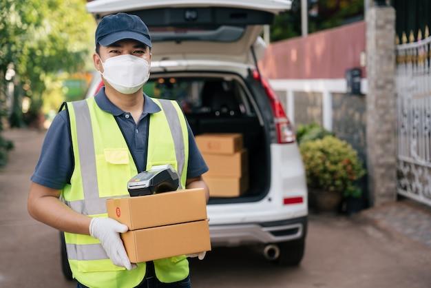 Heureux livreur tenant des boîtes et un lecteur de carte de crédit portant des masques pour empêcher la propagation du coronavirus ou du covid-19