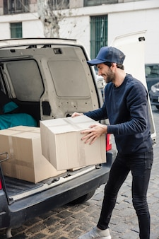 Heureux livreur transportant une boîte en carton près du véhicule