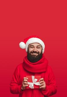 Heureux mâle barbu adulte en bonnet de noel et écharpe tenant un petit cadeau
