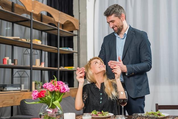 Heureux mâle près de femme joyeuse à la table