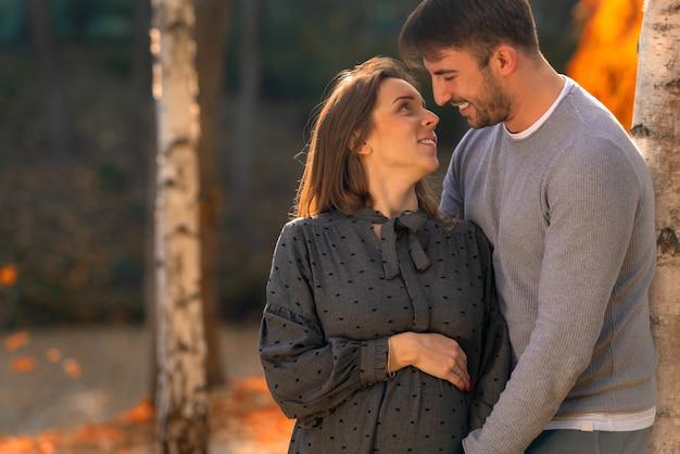 Heureux mari aimant souriant à sa femme enceinte alors qu'ils se détendent dans un parc dans la lumière du soir à l'automne dans un portrait en gros