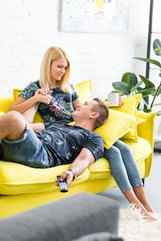 Heureux mari allongé sur le canapé sur les genoux de l'épouse