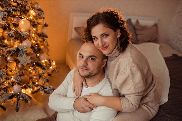 Heureux mari et femme de famille s'embrassent à la maison sur le lit près de l'arbre de noël.