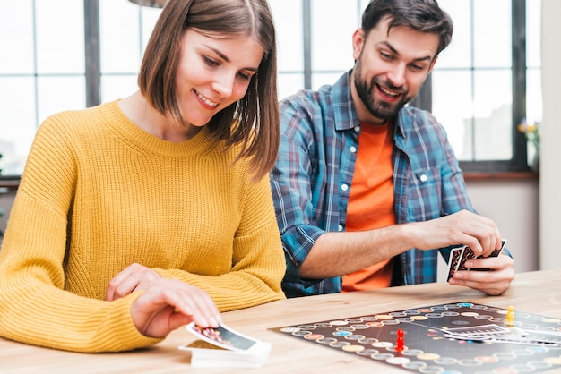 Heureux mari et femme jouant au jeu de cartes de visite