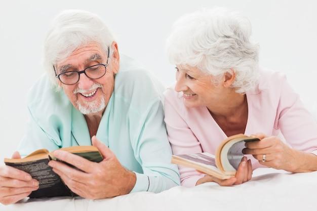 Heureux mari et femme lisant dans son lit