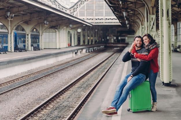 Heureux mari et femme mal rasés s'embrassent à la gare, vont faire un voyage, prennent des vacances.