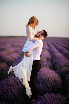 Heureux marié tenant sa mariée dans ses bras dans un champ de lavande en fleurs au coucher du soleil