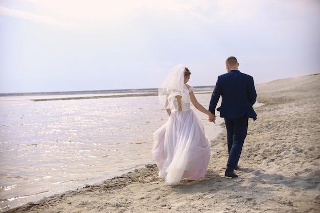 Heureux mariés courent le long du lac de la rive