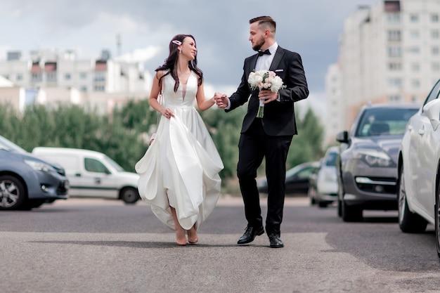 Heureux mariés marchant dans la rue de la grande ville. vacances et événements