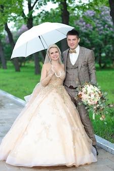 Heureux mariés avec un parapluie blanc sous la pluie, en été dans le parc. mariage en plein air.