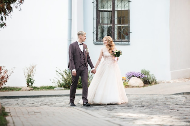 Heureux mariés passant par la rue de la ville.