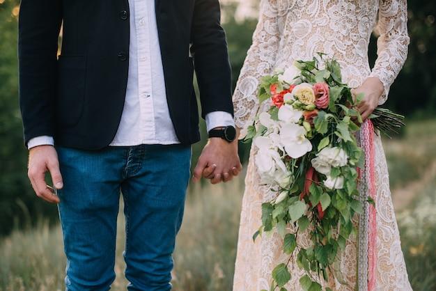 Heureux mariés se tenant la main et marchant dans la nature, gros plan