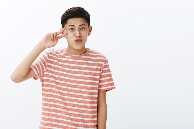 Heureux mec asiatique mignon charismatique avec une coiffure courte souriante lèvres pliantes stupides faisant signe de paix près du visage