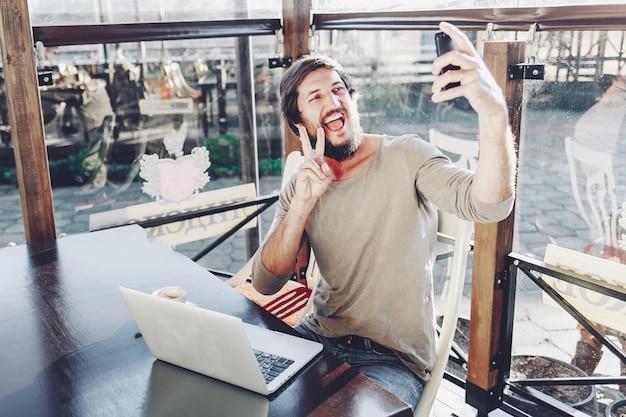 Heureux mec attrayant faisant selfie montrant le geste de la victoire et souriant.