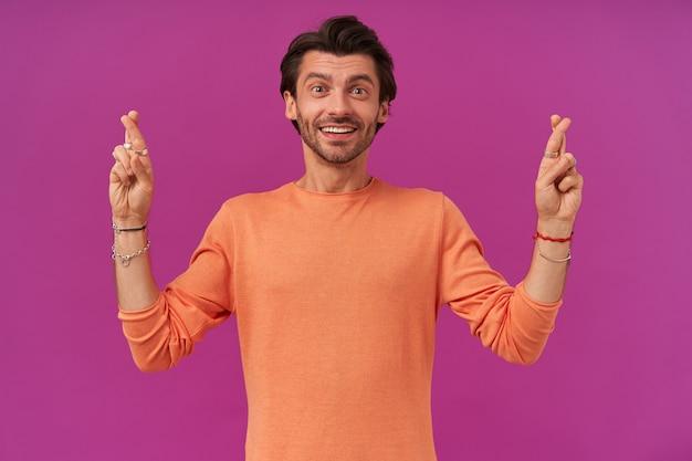 Heureux mec aux cheveux et soies brune. porter un pull orange à manches retroussées. a des bracelets et des bagues. garde les doigts croisés