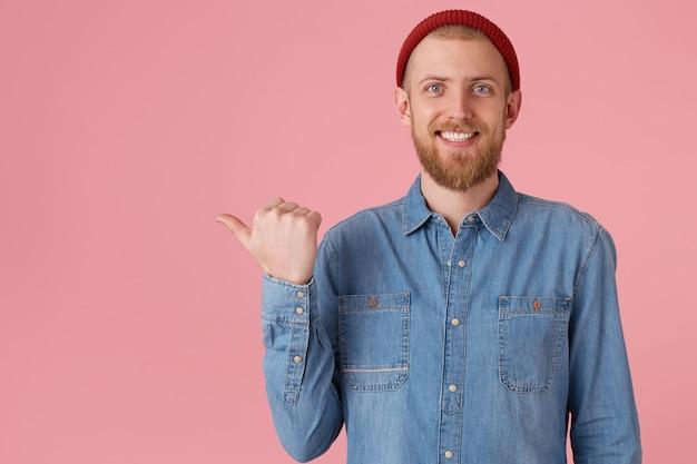 Heureux mec aux yeux bleus en chapeau rouge avec une barbe épaisse rouge ressent la joie joie montrant des dents blanches en bonne santé, en chemise en jean, isolé sur des points de mur rose avec le pouce vers le côté gauche sur l'espace de copie