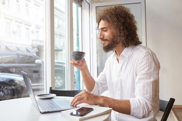 Heureux mec barbu attrayant assis à table à côté de la fenêtre avec un ordinateur portable, regardant l'écran joyeusement et ayant une tasse de thé, portant une chemise blanche