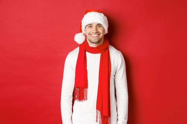Heureux mec caucasien célébrant noël et souriant portant une écharpe de bonnet de noel et un chandail blanc enjo...