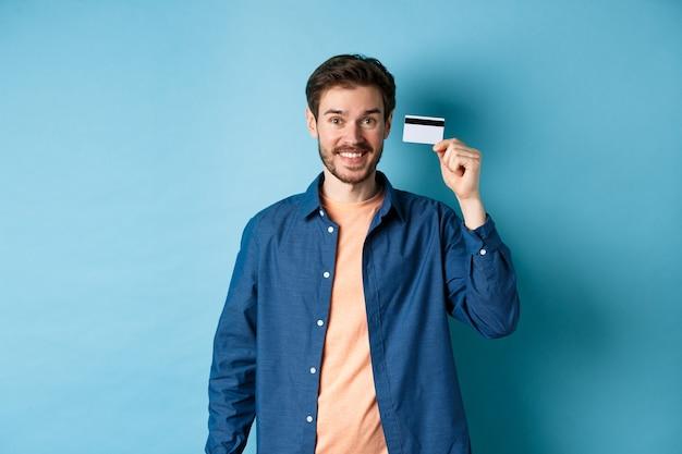 Heureux mec caucasien souriant, montrant une carte de crédit en plastique, debout dans des vêtements décontractés sur fond bleu.