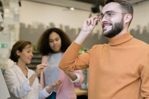 Heureux mec essayant une paire de lunettes sur consultant aidant une jeune cliente
