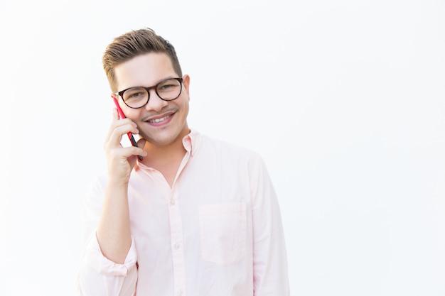 Heureux mec gai à lunettes chat sur téléphone portable