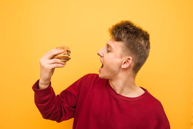 Heureux mec avec un hamburger appétissant dans ses mains est isolé sur un jaune
