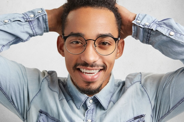 Heureux mec hipster dans de grandes lunettes rondes se sent détendu