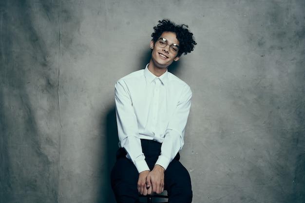 Heureux mec avec des lunettes chemise blanche pantalon studio de photographie posant modèle
