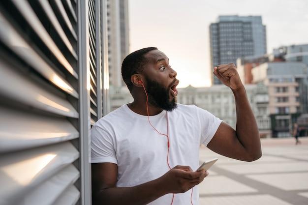 Heureux mec portant des vêtements décontractés dansant sur la rue urbaine. homme américain africain, écouter musique, dehors
