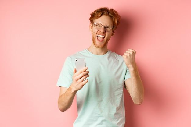 Heureux mec rousse à lunettes et t-shirt gagnant le prix en ligne, criant oui avec joie et satisfaction, tenant un smartphone et faisant une pompe à poing, fond rose.