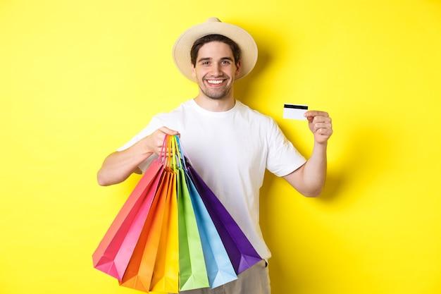 Heureux mec séduisant montrant des sacs à provisions et une carte de crédit, concept de banque et paiement facile, debout sur fond jaune